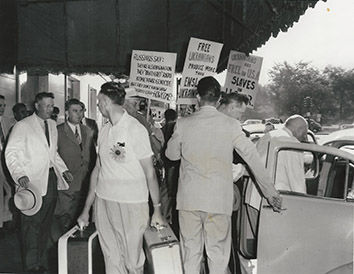 1955, August 13. GA. Chicago, Illinois. SOVIET FARM GROUP PICKETED. Soviet farmer group picketed by immigrants from Estonia, Lithuania, Ukraine and Baltic region. Vladimir Matskevich, Soviet farm chief, entering cab at extreme right. AP Photo (Front)
