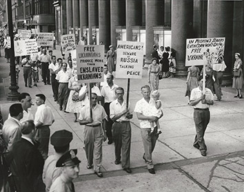 1955, August 15. HA. Chicago, Illinois. More than two dozen Ukrainian pickets march in front of Michigan Avenue office building where the members of the Russian farm delegation held a press conference. United Press Photo (Front)