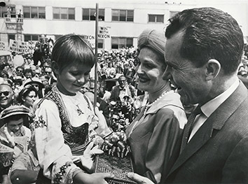 1960, July 25. BA. Chicago, Illinois. DISTINGUISHED VISITORS RECEIVE A PRESENT. Vice President Nixon and Mrs. Nixon receive a gift from girl in Ukrainian native attire at the Republican Convention. AP Wirephoto (Front)