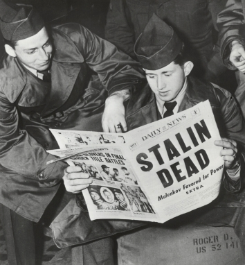 1953, March 5. BA. New York, New York. Two soldiers, waiting to board trains in Pennsylvania Station, late 3/5, read about the death of Russian Premier Josef Stalin and display different reactions. Alex Fenton (left) of Pittsburgh leans on Roger Green of East Liverpool, who holds the newspaper. UNITED PRESS (Front)