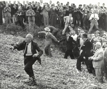 1959, October. JA. Coon Rapids, Iowa. BARNYARD FLING. Farmer Roswell Garst, host to Soviet Premier Khrushchev, right, hurled cornshucks at some of swarm of newsmen crowding around as he led the Russian leader ontour of his Iowa acres in Sept. 1959. Walking along with Khrushchev was Henry Cabot Lodge, dark suit and glasses, then U.S. Ambassador to the United Nations. AP Wirephoto. (Front)